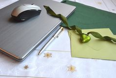 Laptop computer with a green note card and green Christmas ornament. Flt layout royalty free stock image