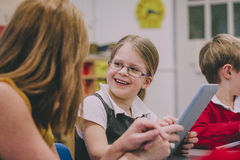 Technology In The Classroom. Primary school students are using digital tablets in their classroom lesson. A little girl is looking at her teacher and laughing Royalty Free Stock Photos