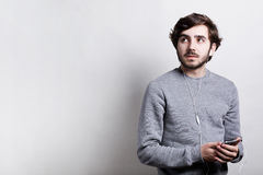 Technology and communication concept. Young stylish man with beard  wearing grey sweater listening to music on white earphones usi. Ng his smartphone looking up Royalty Free Stock Photo