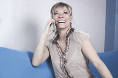 Technology, communication - happy young woman calling on smartphone and laughing at home Royalty Free Stock Photos