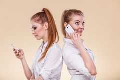 Girls using mobile phones talking reading message. Technology and communication. Lovely teen girls sharing social media, using mobile phones talking and looking Royalty Free Stock Photography