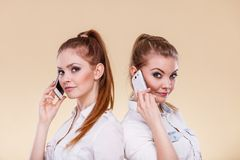 Girls using mobile phone talking. Technology and communication. Lovely teen girls using mobile phones talking, Human emotion, reaction and relationship Royalty Free Stock Images