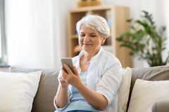 Happy senior woman with smartphone at home stock photography
