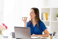 Woman using voice recorder on smartphone at office. Technology, communication and people concept - happy woman using voice command recorder on smartphone at stock photos