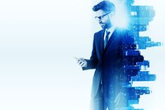 Technology concept. Side view of handsome young businessman using smartphone on abstract glowing white city background with copy space. Technology concept Royalty Free Stock Photography