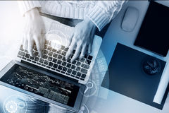 Technology concept. Top view of young woman using laptop with digital charts and diagram placed on her lap. Supplies and computer mouse next to her. Technology Stock Photos