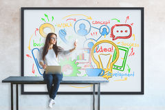 Technology concept. Young woman with laptop taking selfie while sitting on table. Business sketch in frame on concrete wall in the background. Technology concept Stock Photo