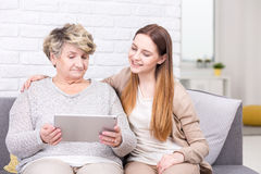 Technology is created for everyone. Shot of a grandmother and her granddaughter looking at a tablet Royalty Free Stock Images