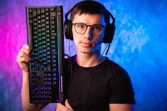 Technology, cyberspace, programming and people concept - hacker man in headset and eyeglasses with keyboard over neon stock images
