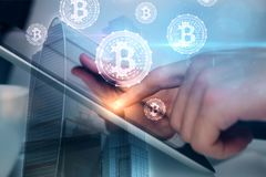 Technology and e-commerce concept. Side view of businessman hand using tablet with bitcoins on abstract city background. Technology and e-commerce concept Stock Images