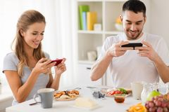 Couple with smartphones having breakfast at home Stock Image