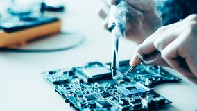 Technology education solder motherboard component. Technology microelectronics science education. Engineer student learning to solder electronic component on stock photos