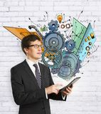 Technology, engineering and leadership concept. Businessman using tablet with abstract cogwheel business sketch. Technology, engineering and leadership concept Royalty Free Stock Image