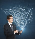 Technology, engineering and plan concept. Businessman using tablet with abstract cogwheel business sketch. Technology, engineering and plan concept Stock Photos