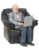 Technology is for everyone. Image of a senior man siting in an armchair and using a laptop,isolated against a white background Stock Image