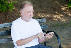 Technology for everyone. Closeup portrait of bold elderly man in white shirt, squinting, checking smartphone, sending text message, seated on a bench, isolated Royalty Free Stock Photo