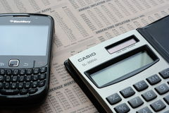 Technology on finance. Blackberry mobile phone and casio calculator against finance page silver and black daylit Stock Photography