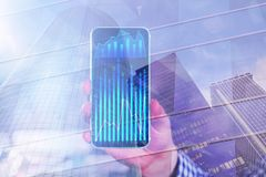 Technology and finance concept. Hand holding smartphone with business chart on abstract city background with forex diagram. Technology and finance concept Royalty Free Stock Image