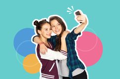 Happy teenage girls taking selfie with smartphone stock images