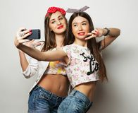 Technology, friendship and people concept - two smiling teenagers taking picture with smartphone camera. Technology, friendship and people concept - two smiling royalty free stock image