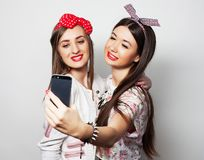 Technology, friendship and people concept - two smiling teenagers taking picture with smartphone camera. Technology, friendship and people concept - two smiling stock photos