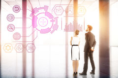 Technology, future, innovation and analytics concept. Back view of young businessman and women looking at digital business hologram in bright office interior royalty free stock image