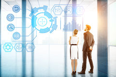 Technology, future, innovation and communication concept. Back view of young businessman and women looking at digital business hologram in bright office interior royalty free stock photography