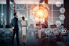 Technology, future, innovation and network concept. Back view of young businessman and women looking at digital business hologram in night office. Technology royalty free stock photos