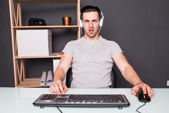 Technology, gaming, entertainment, let`s play and people concept - angry screaming young man in headset with pc computer playing. Angry screaming young man in Stock Photo