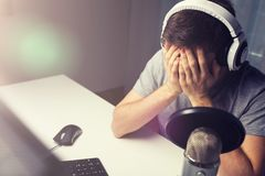 Close up of man losing computer video game. Technology, gaming, entertainment, let`s play and people concept - close up of sad young man in headset with pc Royalty Free Stock Photo