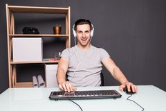 Technology, gaming, entertainment, let`s play and people concept - screaming young man in headset with pc computer playing game a. Angry screaming young man in Royalty Free Stock Photo