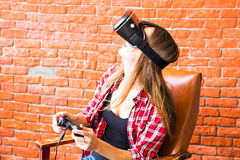 Technology, gaming, entertainment and people concept - young woman with virtual reality headset, controller gamepad Royalty Free Stock Images