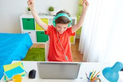 Boy with headphones playing video game on laptop. Technology, gaming and people concept - boy with headphones playing video game on laptop computer and Stock Photo