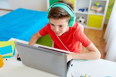 Boy in headphones playing video game on laptop. Technology, gaming and people concept - boy in headphones playing video game on laptop computer at home Stock Image