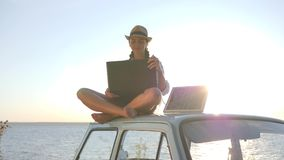 Technology, girl in vacation sits on roof blue car with solar array charges laptop in backlight, female sitting on. Vintage car with computer and battery stock video footage