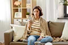 Sad sick woman in blanket using smartphone at home. Technology, health and cold concept - sad sick woman in blanket using smartphone at home royalty free stock photo