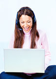 Technology at home. Happy young woman with headphones and laptop at home stock photography