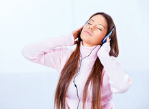 Technology at home. Pretty young woman with headphones listening music at home stock photo
