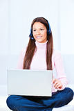 Technology at home. Pretty young woman with headphones and laptop at home royalty free stock photography