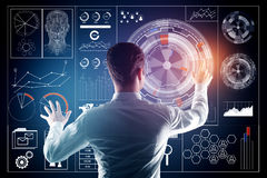 Technology, innovation and analytics concept. Back view of young businessman managing abstract business chart hologram. Technology, innovation and analytics royalty free stock image