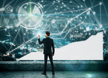 Technology, innovation and communication concept. Back view of young businessman drawing abstract glowing digital business hologram on concrete roofrop with Royalty Free Stock Photos