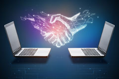 Technology, innovation and teamwork concept. Two laptops with abstract polygonal handshake. Technology, innovation and teamwork concept. 3D Rendering Stock Photos