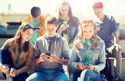 Happy teenage friends with smartphones outdoors royalty free stock photo