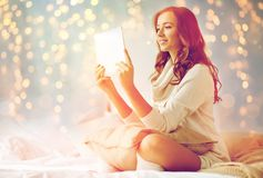 Happy young woman with tablet pc in bed at home Royalty Free Stock Photos