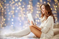 Happy young woman with tablet pc in bed at home Stock Images