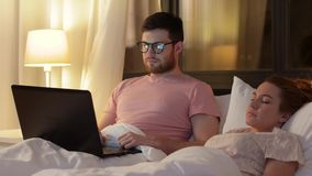Man using laptop while girlfriend is sleeping. Technology, internet and communication concept - man in glasses using laptop computer in bed at night while his stock video footage