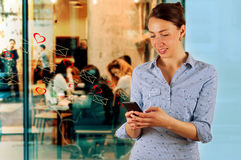 Technology, internet, communication and people concept - happy smiling young woman texting Stock Image