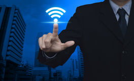 Technology and internet concept. Businessman pointing to wi-fi button over modern office city tower, Technology and internet concept Royalty Free Stock Photos