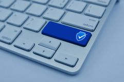 Technology internet cyber security and anti virus concept. Security shield with check mark flat icon on modern computer keyboard button, blue tone, Technology royalty free stock photography