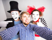Technology internet and happiness concept. Young men and mime taking self picture selfie with smartphone camera gray Royalty Free Stock Photo